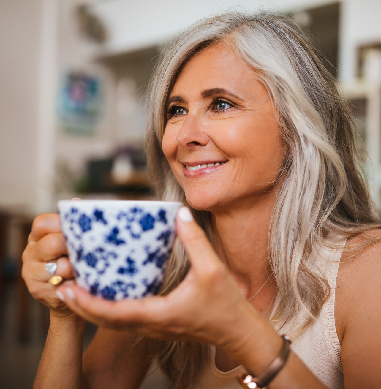 smiling older woman holding tea cup